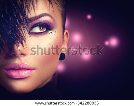 Sexy model girl face close up with holiday bright purple make up over black background. Beauty woman with vivid makeup and feather hairstyle. Beautiful Glamour lady. Party style - stock photo