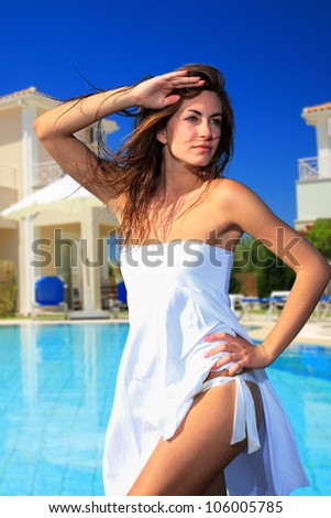 Sexy  model posing by the swimming pool at summer resort