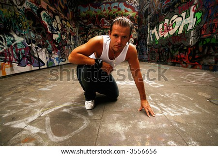 Sexy Model posing in front of urban graffiti sprawl - stock photo