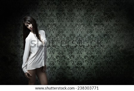 sexy model posing with damascus wallpaper behind - stock photo