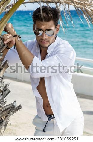 Sexy model under the palm tree wearing aviator sunglasses - stock photo