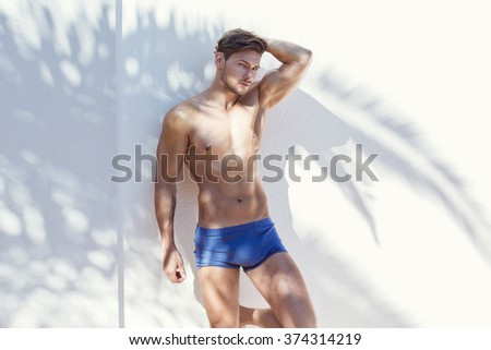 Sexy model wearing blue swimming trunks and posing  - stock photo