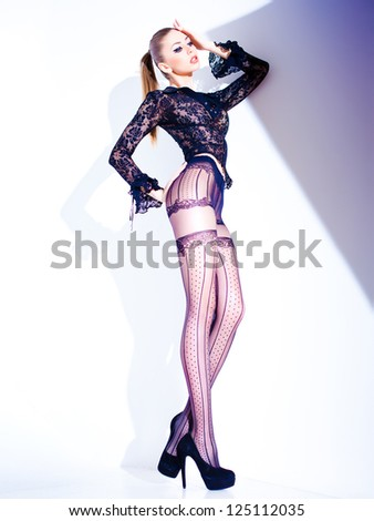 sexy model with long legs dressed in lace blouse and elegant tights posing - fashion shoot - stock photo