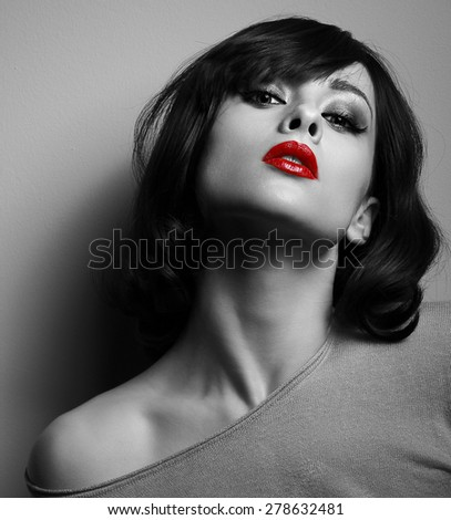 Sexy model with short hair style and red lips posing on dark background. Black and white - stock photo