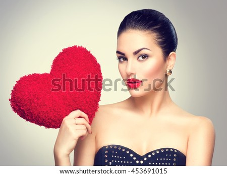 Sexy model Woman portrait. Gorgeous young brunette woman holding heart shaped red pillow. Perfect make up. In love - stock photo