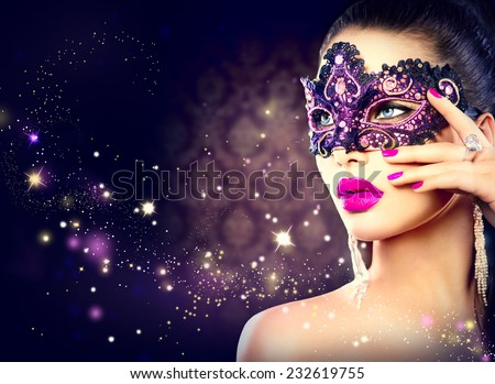 Sexy model woman wearing venetian masquerade carnival mask at party over holiday dark background. Christmas and New Year celebration. Sexy girl with holiday makeup and manicure. Purple lips and nails - stock photo