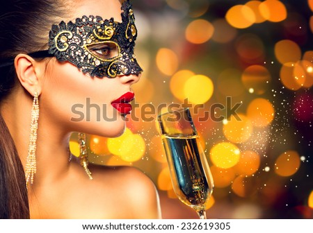 Sexy model woman with glass of champagne wearing venetian masquerade carnival mask at party, drinking champagne over golden holiday glowing background. Christmas, New Year celebration. Perfect make up - stock photo