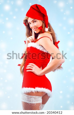 Sexy mrs. Santa smiling and posing on blue winter background with snowflakes - stock photo