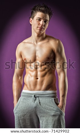 Sexy muscle wet young man on purple background - stock photo