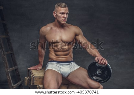 Sexy muscular guy in a white panties sits on a wooden box and holds lifting weights.