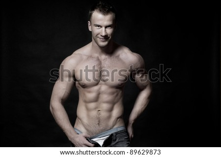 Sexy muscular macho man  in jeans photographed on black background - stock photo