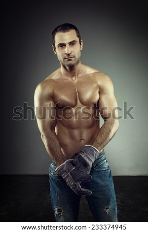 Sexy muscular macho worker in gloves posing - stock photo