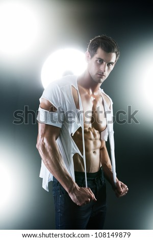 Sexy muscular male in white ripped shirt in studio - stock photo