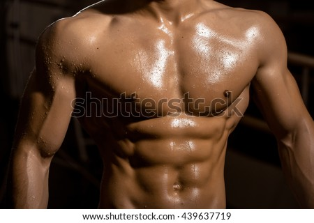 sexy muscular male torso six packs on wet body of athletic man training with bare chest and strong biceps on hands, closeup - stock photo