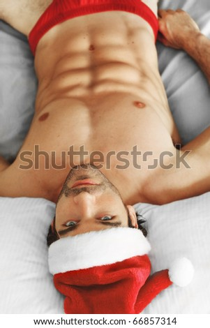 Sexy muscular man laying shirtless in bed with a Santa cap and red shorts - stock photo