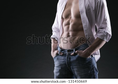 Sexy muscular man on dark background - stock photo