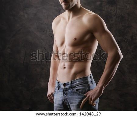 Sexy muscular man on dark background - stock photo