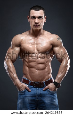 Sexy muscular man wearing the jeans on dark background - stock photo