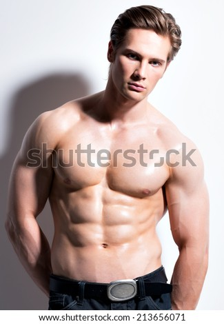 Sexy muscular young man looking at camera posing on a white background with contrast shadows. - stock photo
