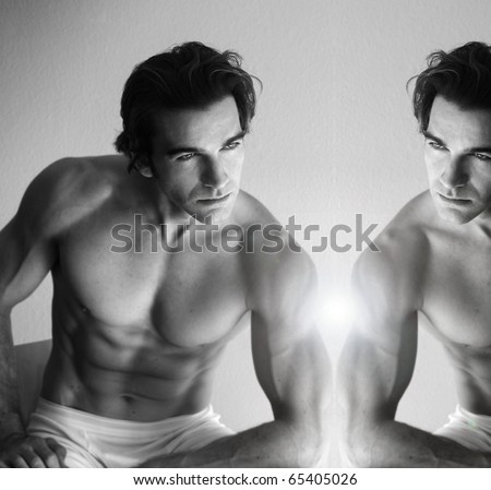 Sexy muscular young man looking in mirror - stock photo