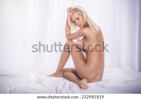 Sexy naked blonde woman in bed, looking at camera. Perfect body. - stock photo