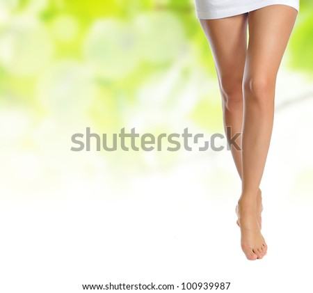 sexy naked slender female legs making step over green natural background
