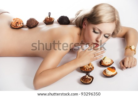 sexy naked woman with long blond hair laying down on white with some pastry near her in act to eat them, she has some pastries on her back.