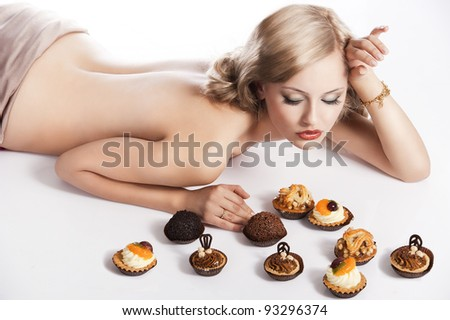 sexy naked woman with long blond hair laying down on white with some pastry near her in act to eat them, she looks the pastries and has right hand near the head - stock photo