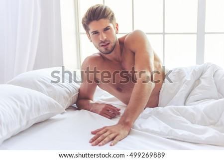 Sexy naked young man is looking at camera while lying in bed