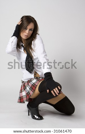 sexy naughty brunette school girl in plaid skirt and black stockings and tie - stock photo