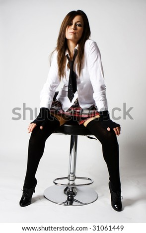 sexy naughty brunette school girl in plaid skirt and black stockings and tie sitting on a nice chair - stock photo