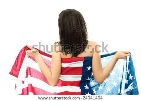 sexy nude brunette woman wearing an American flag standing with her back to us and unwrapping the flag - stock photo