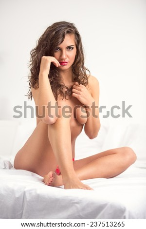 Sexy nude woman sitting on bed  - stock photo