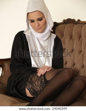 Sexy nun on a sofa - stock photo