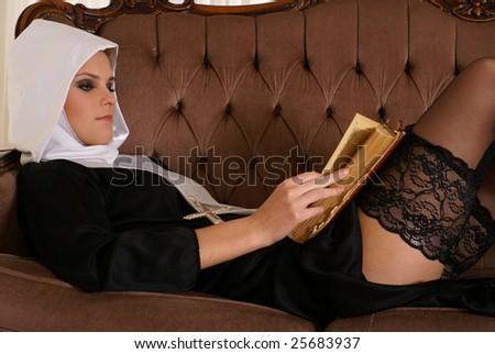 Sexy nun reading Bible - stock photo