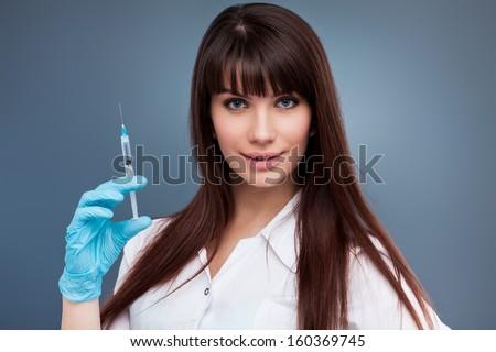 Sexy nurse holding syringe on blue background - stock photo