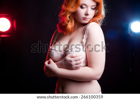 Sexy overweight woman in studio on black background with two light behind her. Chubby but sexy woman - stock photo