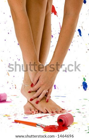 Sexy pair of feet and hands surrounded by colorful paint splatter. - stock photo