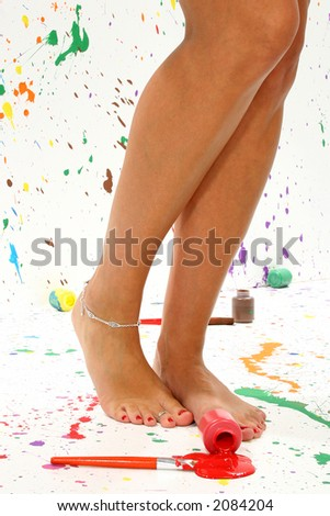 Sexy pair of legs in paint in paint splattered studio.