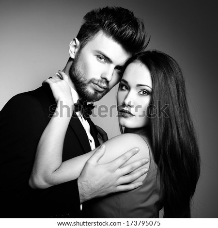 Sexy passion couple in love. Portrait of beautiful young man and woman dressed in classic clothes, studio shot over grey background  - stock photo