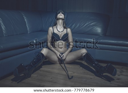 Sexy passionate woman in blindfold and latex boots holding whip on floor, bdsm
