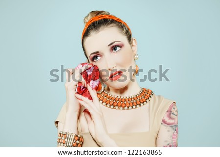 sexy pin-up girl crying holding a tissue. Vintage style on light blue background. - stock photo