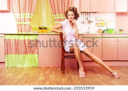 Sexy pin-up girl wearing pink bathrobe alluring on her pink kitchen at home. Fashion. Full length portrait.