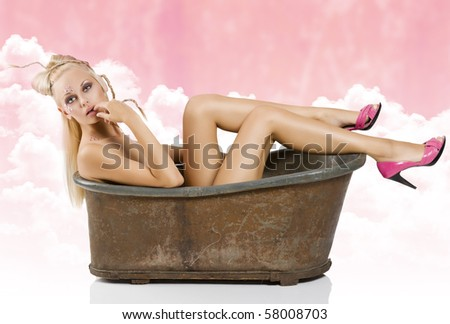 sexy pin up inside an old fashion bath with creative hair style and stone on face and pink shoes - stock photo