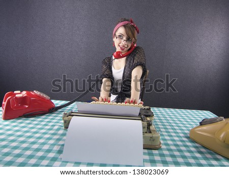 Sexy pin up secretary sitting at a desk talking on phone and typing on typewriter - stock photo