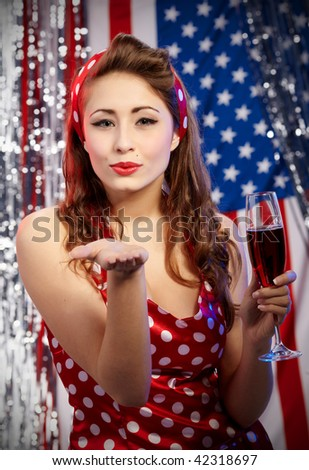 Sexy pin-up woman with champagne over american  flag - stock photo