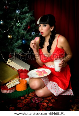 sexy pinup girl eating Santa's cookies - stock photo