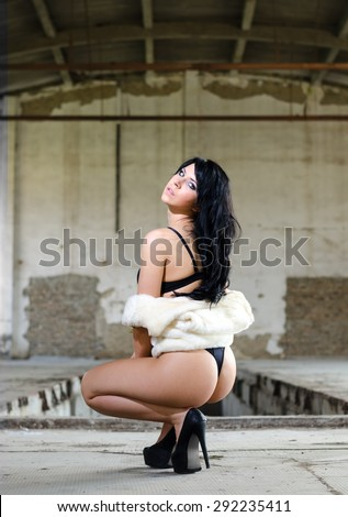 Sexy pinup girl in underwear and white fur coat posing in abandoned building. - stock photo