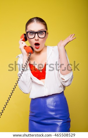 Sexy playful young woman talking on the phone.