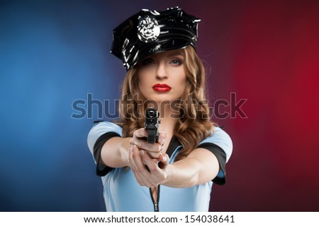 Sexy policewoman. Beautiful young policewoman aiming you with a gun while isolated on colored background - stock photo